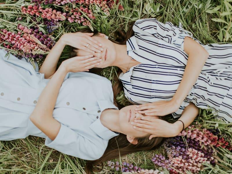 兩個女生頭對著頭躺在草地上